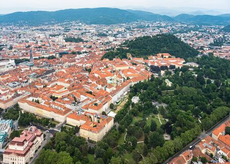 Aerial view of center city Graz from helicopter drone with hill Schloßberg, tower Uhrturm and central park on a summer day in Austria, Europe