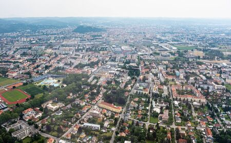 Aerial view of city Graz from helicopter drone with district Eggenberg with swimming pool on a cloudy summer day in Austria, Europe