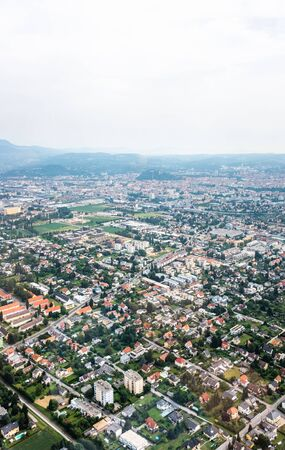 Aerial view of city Graz from helicopter drone with districts Eggenberg and Wezelsdorf on a cloudy summer day in Austria, Europe