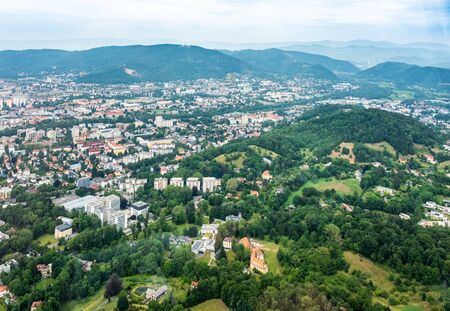 Aerial view of city Graz from helicopter drone with district Geidorf with hill Reinerkogel on a cloudy summer day in Austria, Europe Stock Photo