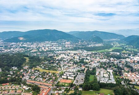 Aerial view of city Graz from helicopter drone with district Andritz with hill Reinerkogel on a cloudy summer day in Austria, Europe