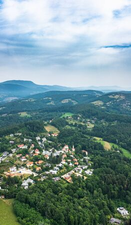 Aerial view of small town Maria Grün with church in city Graz from helicopter drone on a cloudy summer day in Austria, Europe
