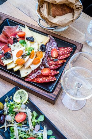 Delicious, fresh antipasti on wooden plate, salad with anchovy and bread in paper in nice restaurant in Italy, Europe Stock fotó