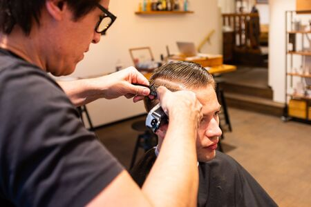 Barber trims the hair of a young man with a razor in his barbershop