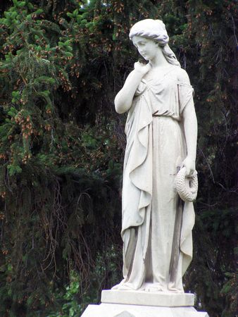 statue of a woman holding a wreath in a cemetery