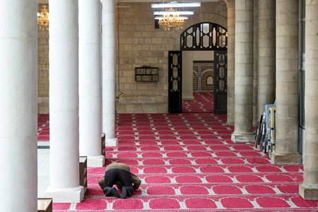 muslim celebration: Amman, Jordan - April 03, 2015: View of a man praying in the Al Husseini Mosque. This mosque was built by the late King Abdullah in 1924 in Ottoman style. It is located in the heart of downtown Amman.