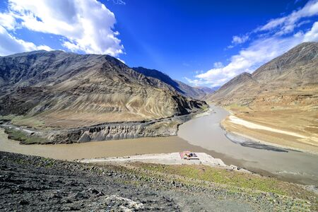 confluence: Panoramic view of confluence of Zanskar from top and Indus rivers near Nimmu village in Ladakh, India.