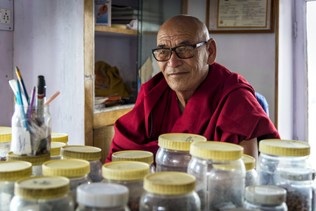 herbalist: Thiksey, India - August 16, 2015: View of the herbalist monk of Thiksey monastery sitting in his laboratory. Some monks do become skilled in herbal medicine and other traditional therapies. Editorial