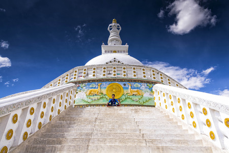 shanti: Leh, India - August 24, 2015: View of a young boy meditating in front of Shanti Stupa. Shanti is a Buddhist white-domed stupa on a hilltop in Chanspa, Leh district. It was built in 1991. Editorial