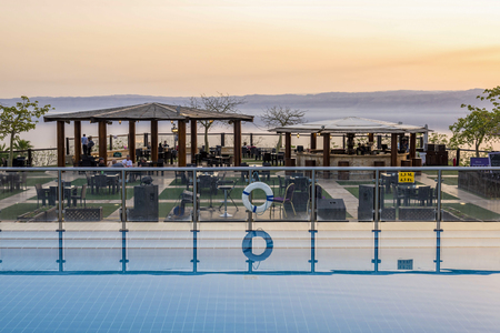sea resort: Sweimeh, Jordan - April 07, 2015: View of sunset over death sea from Horizon Terrace at Holiday Inn Resort Dead Sea. This outdoor bar and restaurant is a relaxed spot at any time of day.