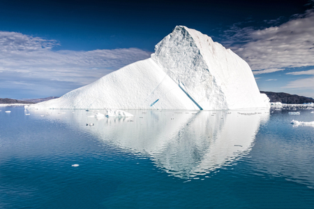 Massive iceberg floating near Eqi Glacier in Greenland. An iceberg is a large piece of freshwater ice that has broken off a glacier or an ice shelf and is floating freely in open water.