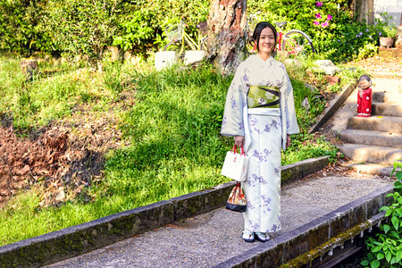 festival moments: Kyoto, Japan - May 01, 2014: View of a Japanese girl wearing traditional Kimono. The kimono is a Japanese traditional garment and is always used in important festival or formal moments