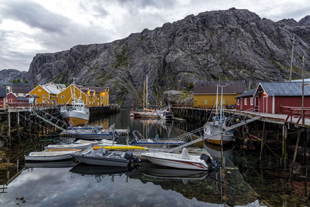 Nusfjord, Norway - August 20, 2016: View of the harbor under dramatic sky. Nusfjord is one of the oldest and best preserved fishermen village of Norway. It is located on the Lofoten Islands