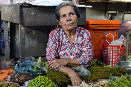 Phnom Penh, Cambodia - December 31, 2016: Unidentified elder woman selling vegetable in Toul Tom Poung Market, also called Russian Market Editorial