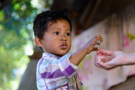 Koh Ker, Cambodia - January 02, 2017: Portrait of a child who take a snack offered by a tourist in the famous archaeological site of Koh Ker