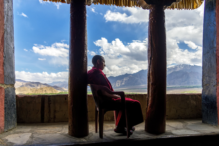 Thikse, India - August 16, 2015: A buddhist monk with red robe on a chair resting in Thikse gompa (monastery). This monastery is affiliated with the Gelug sect of Tibetan Buddhism 新聞圖片