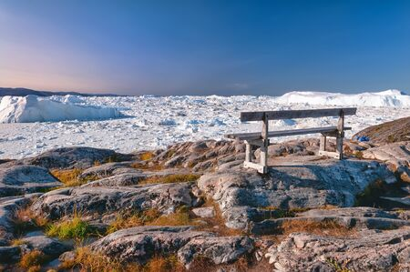 The lonely bench on the hiking trail to Sermermiut, Greenland. Sermermiut was an Inuit settlement near the town of Ilulissat, in the Disko Bay. Here, in front of the Icefjord stay this famous bench Standard-Bild