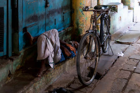 Kumbakonam, India - August 21, 2018: Old man is resting lying in front of a closed shop in the Kumbakonan bazar