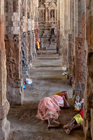 Srirangam, India - August 22, 2018: Pilgrims resting on the ground in Ranganathaswamy Temple. Often it is possible to observe the pilgrims resting among the elaborate columns