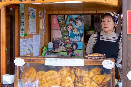 Takayama, Japan - April 26, 2014: Saleswoman inside his senbei store at the Miyagawa morning market. Senbei are a type of Japanese rice cracker Editorial