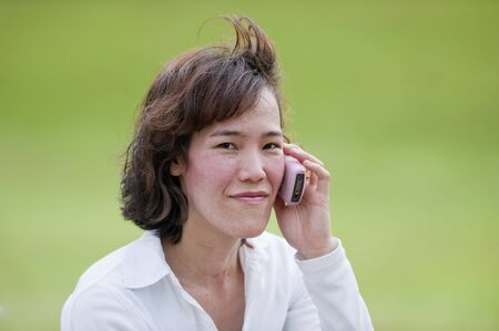 pone: Portrait of a young Asian businesswoman listening to her cell pone and smiling to the camera.  Stock Photo