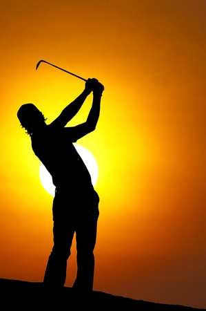 A male golfer enjoys an early round during sunrise.  写真素材