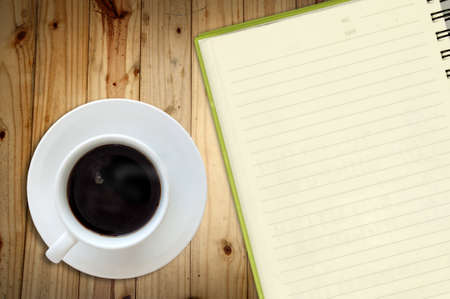 White cup of hot coffee and white sketch book on wood table  Stock Photo - 9077106