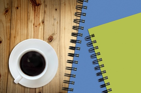 White cup of hot coffee and white sketch book on wood table Stock Photo - 9077101