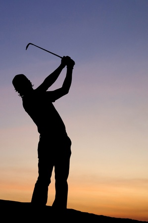A male golfer enjoys an early round during sunrise.  Stock Photo