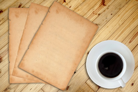White cup of hot coffee and white sketch book on wood table  photo