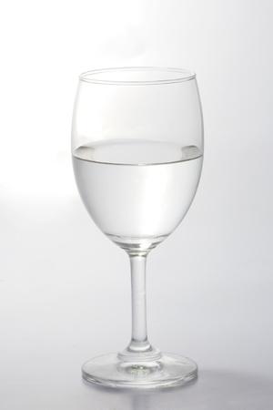 cristalería: Vaso de agua medio vac�o aislado sobre fondo blanco  Foto de archivo