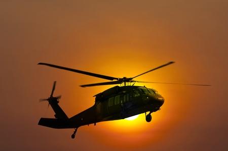 日没の着陸のヘリコプター 写真素材