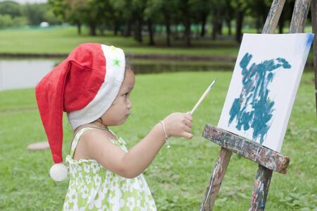 little girl. Are painting pictures in the park. photo