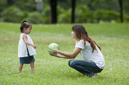 Mother teaching daughter to soccer/ball in the park happily. Stock Photo - 9673677