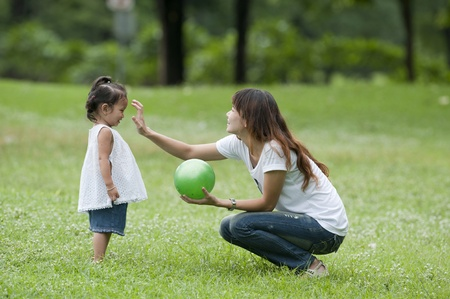 Mother teaching daughter to soccerball in the park happily.
