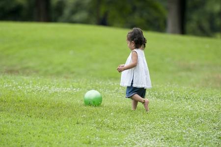 公園内の小さな少女プレイ ゲーム 写真素材