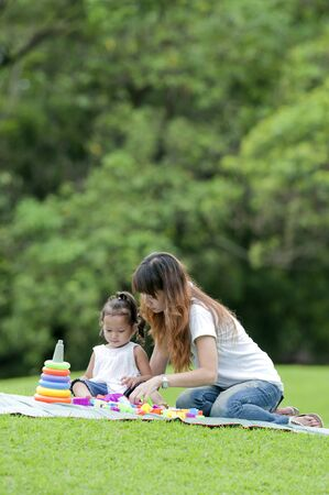 Mother teaching daughter to soccer/ball in the park happily. Stock Photo - 9673629