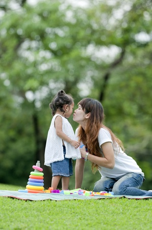 Mother teaching daughter to soccerball in the park happily. photo