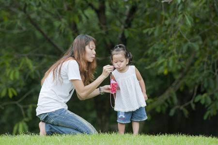 母娘は公園でサッカー ・ ボールを喜んで教えます。