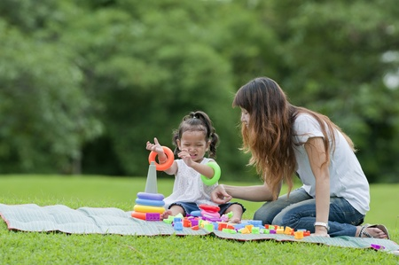Little girl and her mother were playing toys in the garden.  photo