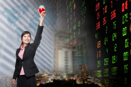Smiling business woman standing holding a glass of champagne. over stock exchange background  photo