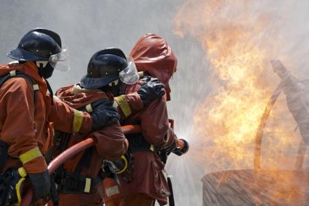 manguera: Bomberos luchando por un ataque de fuego, durante un entrenamiento Foto de archivo