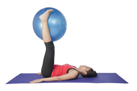 Young beautiful woman during fitness time and exercising with blue ball, isolated on white background  photo