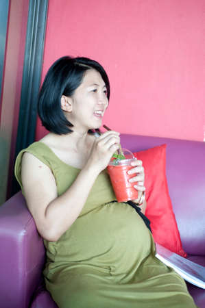 Healthy pregnant woman drinking glass with strawberry juice  photo
