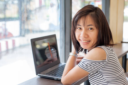 Business woman using computer sitting in a cafe with cocoa spin put on the right hand side. photo