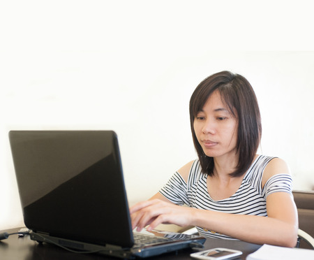 Woman sitting use computer on wooden table at home office ,background of green trees. photo