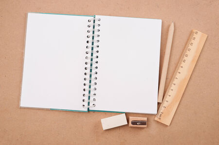 open diary or photo album book on brown backgroun has pencils, erasers, rulers photo