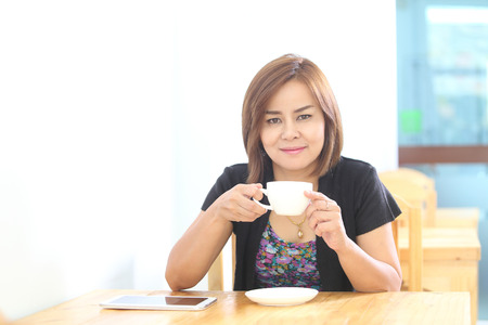 woman drinking coffee in the morning at restaurant photo