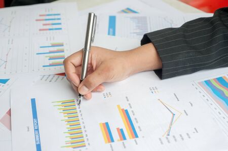backgruond: Businesswoman examine finance, tax, accounting, statistics and analytic research concept Stock Photo