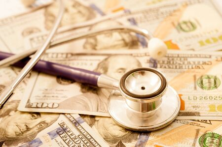health care provider: Stethoscope on a pile of money, depicting the health care industry concept
